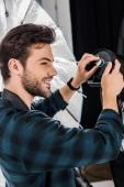 krásný usměvavý mladý fotograf pracuje s profesionální osvětlovací zařízení ve fotoateliéru