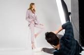 giovane fotografo menzogne e tiro bello modello femminile che posa in studio fotografico