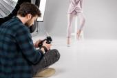Fotografia fotografo che si siede con fotocamera e giovane modella in posa in studio fotografico