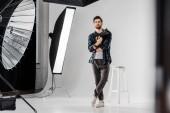 Fotografie voller Länge Ansicht überzeugt junge Fotografen halten professionelle Kamera und Blick in die Kamera im Fotostudio