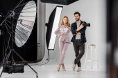 Fotografie junge Fotografen Kamera und schöne weibliche Modell stehen gemeinsam im Fotostudio