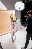 photographer shooting attractive young female model posing with flowers in photo studio