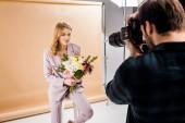 Fotografia bella giovane donna in posa con i fiori in studio della fucilazione del fotografo