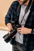 Fotografie oříznutý snímek mladého fotografa drží fotoaparát profesionální foto Studio