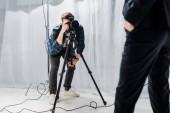 Fotografie oříznutý snímek mladý fotograf fotografování krásný ženský model ve fotoateliéru
