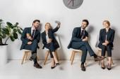 Fotografie koláž s úsměvem mladých podnikatelů s smartphone a papírové košíčky, čekání na židlích v řádku