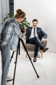 Rückansicht eines jungen Fotografen, der Fotos von gut aussehenden lächelnden Geschäftsmann im Büro macht