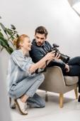 Fotografia Fotografo femminile sorridente e uomo daffari bello utilizzando la macchina fotografica in studio fotografico