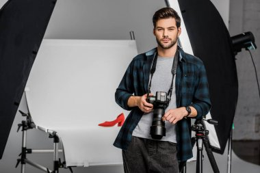 Handsome professional young photographer looking at camera in studio stock vector