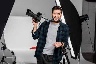 Happy handsome young photographer holding professional photo camera in studio stock vector