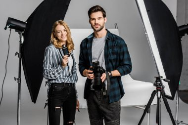 young photographers with professional equipment standing together and smiling at camera in photo studio