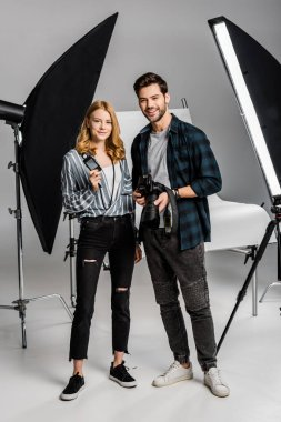 happy young photographers with professional equipment standing together and smiling at camera in studio