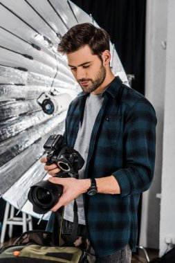 Handsome young photographer holding professional photo equipment in studio stock vector