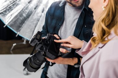 Cropped shot of photographer and model using photo camera together stock vector