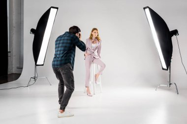 back view of photographer shooting beautiful young female model in photo studio