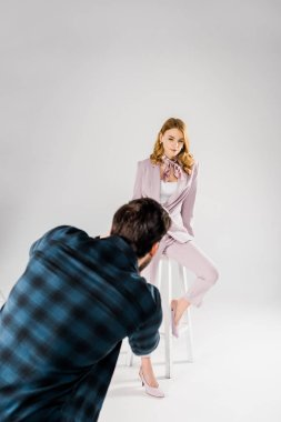 back view of photographer working with beautiful young female model in photo studio