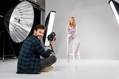 photographer sitting and smiling at camera while beautiful female model posing in studio