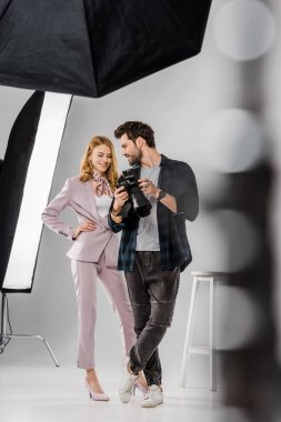 Selective focus of smiling young photographer and model checking photos on camera in studio stock vector