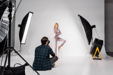 back view of young photographer shooting beautiful female model in studio