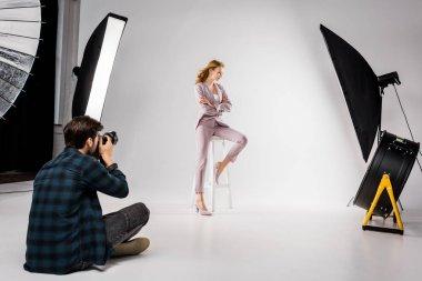 Male photographer shooting beautiful stylish young woman in photo studio stock vector