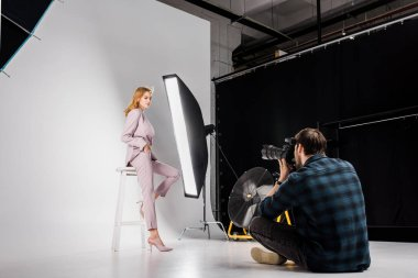 Young photographer sitting and photographing attractive stylish female model in studio stock vector