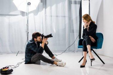 Young male photographer shooting beautiful model in studio stock vector