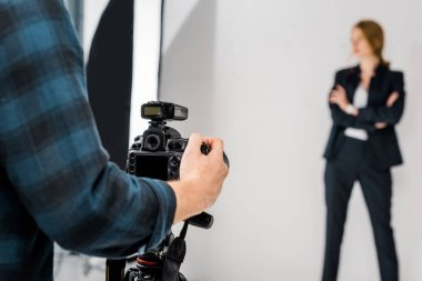 Cropped shot of photographer with camera shooting beautiful model in studio stock vector