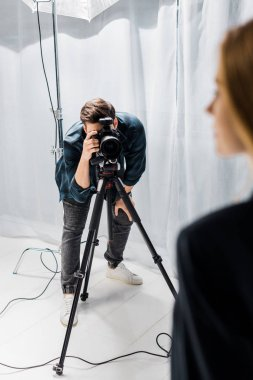 Cropped shot of young photographer shooting beautiful female model in studio stock vector