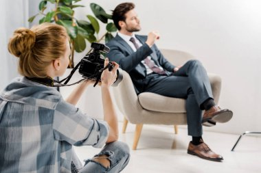 Back view of young female photographer photographing handsome businessman in studio stock vector