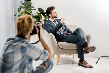 young female photographer photographing handsome businessman in studio