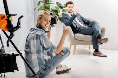 Happy young photographer smiling at camera and showing thumb up while male model sitting behind in studio stock vector