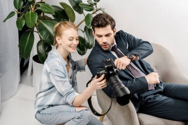 Smiling female photographer and surprised handsome businessman using camera in photo studio stock vector