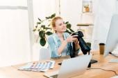 szép mosolygó fiatal fotós kamera gazdaság az irodai munka közben