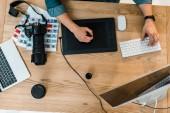 Fotografie Top Teilansicht des jungen Retoucher arbeiten mit Desktop-Computer und tablet