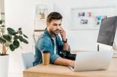 elsősorban fiatal retusáló beszél a smartphone és használ a laptop a munkahelyen