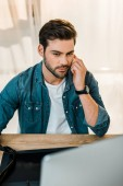 Fotografie handsome young man retouching photos at workplace
