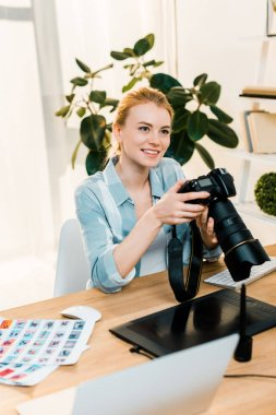 beautiful smiling young photographer holding camera while working in office