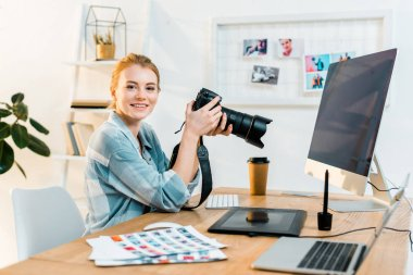 Beautiful young female photographer smiling at camera while working in office stock vector