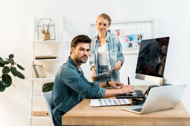 young photographers smiling at camera while retouching photos in office
