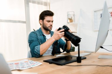 Handsome professional young photographer using camera at workplace stock vector