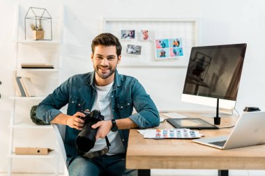 handsome young photographer holding camera and smiling at camera in office