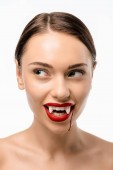 Fotografie smiling naked girl with red lips, vampire fangs and blood on face looking away isolated on white