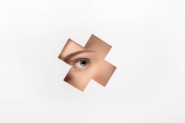 partial view of beautiful girl looking at camera through cross shaped hole on white