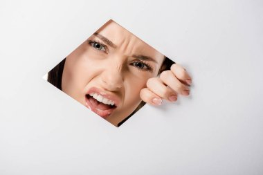 angry young woman looking at camera through hole on white