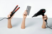 Photo partial view of female hands holding hairstyle tools through holes on white