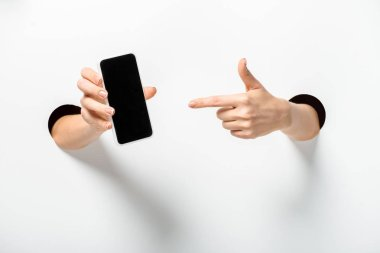 Cropped image of woman pointing on smartphone with blank screen through holes on white stock vector
