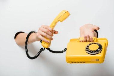 cropped image of woman holding retro yellow stationary telephone through holes on white