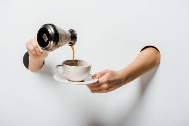 cropped image of woman pouring coffee from cezve into cup through holes on white