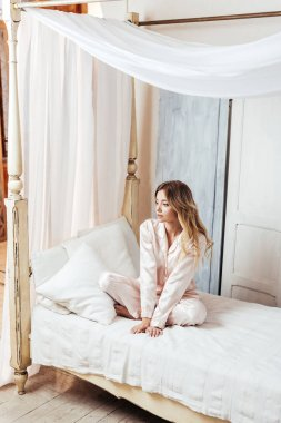 young woman in pajama sitting in bed during morning time at home