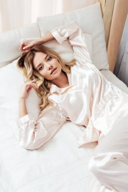 high angle view of girl in pajama resting in bed during morning time at home